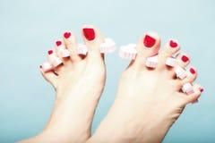 Pédicurie de pied appliquant les ongles de pied rouges sur le bleu Photographie stock libre de droits