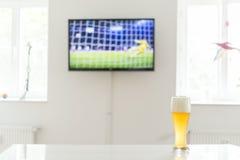 Pénalité du football à la télévision et à un verre de bière de blé sur une table Photo libre de droits