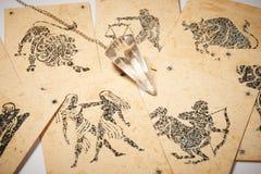 Péndulo cristalino con la tarjeta del zodiaco Foto de archivo libre de regalías