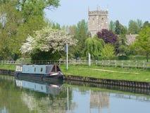 Péniche de canal amarrée par une église Photographie stock