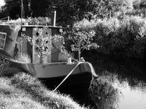 Péniche de canal avec des arbres de petits fruits élevant la rivière Image stock