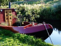 Péniche de canal avec des arbres de petits fruits élevant la rivière Photos stock