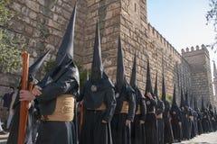 Pénitent avec sa semaine croisée et sainte dans la confrérie de nazaréen de Séville des étudiants photographie stock libre de droits