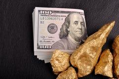Pépites d'or et dollars d'États-Unis sur un cuir noir de fond. Clo Images libres de droits