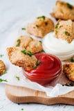 Pépites d'or savoureuses avec des sauces rouges et blanches Photographie stock