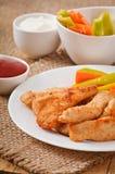 Pépites de poulet avec de la sauce et des légumes Images stock