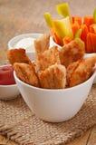 Pépites de poulet avec de la sauce et des légumes Image libre de droits