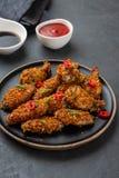 Pépites de poulet avec de la sauce et le poivre sur un fond foncé Copiez l'espace photo libre de droits