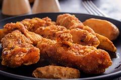 Pépites de poulet d'un plat noir Photographie stock