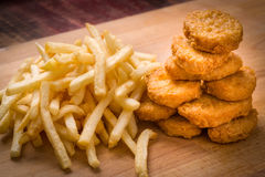 Pépites de poulet et pommes frites brunes d'or sur un backgrou en bois Photos stock
