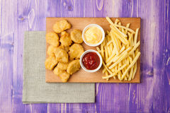 Pépites de poulet, pommes frites et deux tasses avec le ketchup et le fromage sur la table Images stock