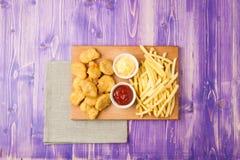 Pépites de poulet, pommes frites et deux tasses avec le ketchup et le fromage sur la table Images libres de droits