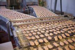 Pépites de poulet sur la bande de conveyeur. Images libres de droits