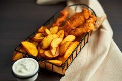 Pépites et pommes de terre cuites au four dans un beau panier avec de la sauce blanche Photos stock