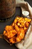 Pépites et pommes de terre cuites au four dans un beau panier avec de la sauce blanche Images stock