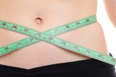 Pérdida de peso. Cinta métrica verde en cuerpo de la mujer Imagen de archivo libre de regalías