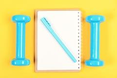 Pérdida de peso y forma de vida activa Equipo del cuaderno, de la pluma y del gimnasio fotos de archivo