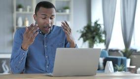 Pérdida, hombre africano joven frustrado que trabaja en el ordenador portátil almacen de metraje de vídeo