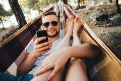 Période de la paresse Un homme se situe dans un hamac et prend des photos de son amie au téléphone Images libres de droits