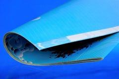 Périodique imprimé d'†de magazine», sur un fond bleu Le journal a un rubrication permanent et contient des articles ou des ess images stock