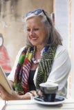 Périphérique mobile unsing de femme mûre en café Photo libre de droits