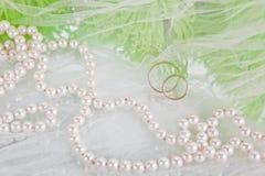 Pérolas, anéis de casamento e ramalhete Imagens de Stock Royalty Free