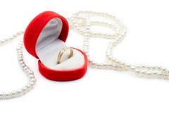 Pérolas e um anel dourado de encontro ao fundo branco foto de stock