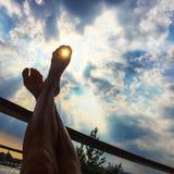 Pés acima no sol