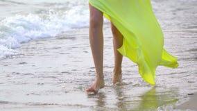 Pés bonitos da moça que vestem o vestido amarelo longo que corre a areia descalça no fim da praia do mar acima das ondas da brisa vídeos de arquivo