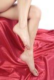 Pés bonitos da mulher sobre o branco com tela vermelha Imagem de Stock