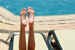 Pés bonitos, pés das meninas, mulheres no fundo de um deckchair e associação em uma estância balnear exótica morna tropical, verã imagem de stock
