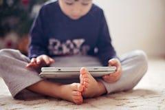 Pés bonitos dos rapazes pequenos, menino que joga na tabuleta Imagens de Stock