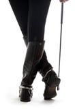 Pés bonitos em carregadores de couro pretos do cavaleiro com chicote Fotos de Stock Royalty Free