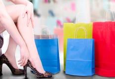 Pés brancos da mulher 'sexy' com a mão que ajusta os saltos altos com sacos de compras Imagens de Stock