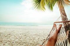 Pés bronzeados bonitos de mulheres 'sexy' relaxe na rede na praia tropical arenosa imagens de stock royalty free