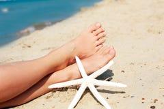 Pés bronzeados bonitos do ` s das mulheres na praia Imagens de Stock
