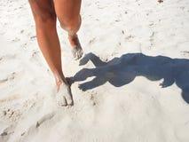 Pés bronzeados que andam na praia branca da areia Fotos de Stock