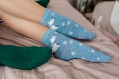 Pés com as peúgas azuis bonitos com ursos brancos e as peúgas verdes na cama Peúgas coloridas fotos de stock royalty free