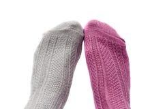 Pés com as peúgas de cores, da cor-de-rosa e do cinza diferentes Fotografia de Stock