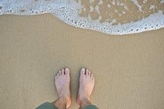 Pés com a onda na opinião superior do Sandy Beach Foto de Stock