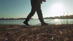 Pés da caminhada do homem perto do rio Pés masculinos que andam na luz do sol perto do rio vídeos de arquivo