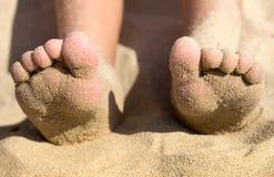 Pés da criança cobertos com a areia na praia, detalhe Imagem de Stock Royalty Free