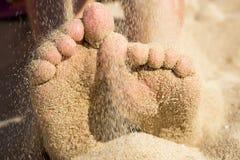 Pés da criança cobertos com a areia na praia, detalhe Foto de Stock Royalty Free