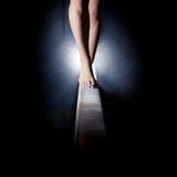 Pés da ginasta no feixe de equilíbrio fotografia de stock