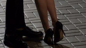 Pés da inclinação fêmea para o homem, do aperto e do beijo na data romântica, amor filme