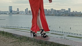 Pés da jovem mulher em um vestido vermelho que anda no vento com vestido de vibração vídeos de arquivo