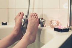 Pés da jovem mulher na banheira Imagem de Stock Royalty Free