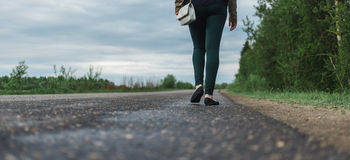 Pés da jovem mulher no vestuário desportivo que anda a estrada de floresta conceito da solidão, incerteza, escolha Fotos de Stock