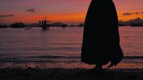 Pés da menina caucasiano que vestem o vestido longo que anda a areia descalça na praia do mar no por do sol Menina que pisa na ar vídeos de arquivo