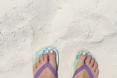 Pés da menina em deslizadores azuis na textura da praia da areia Litoral tropical Molde da bandeira do beira-mar com lugar do tex imagem de stock